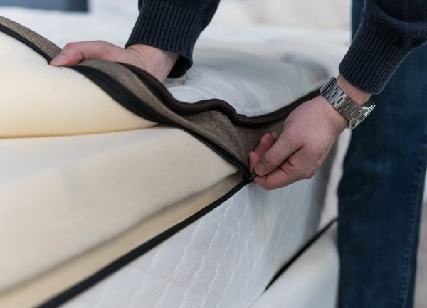 Close-up of hands zipping up a mattress cover